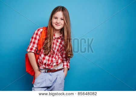 Smiling girl with schoolbag looking at camera