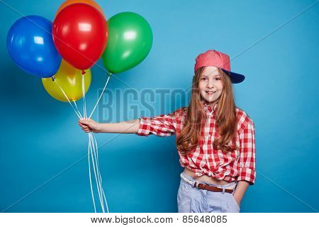 Cute girl keeping balloons on her outstretched hand