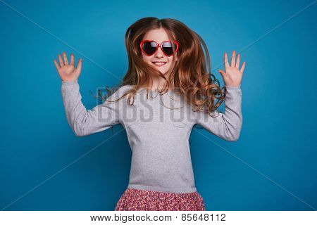 Excited girl in red heart-shaped eyewear jumping
