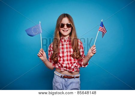 Smiling girl keeping European Union and American flags