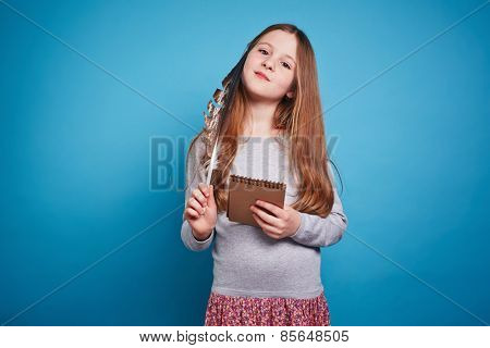 Girl with thoughtful face looking at camera and holding feather pen and notebook in her hands