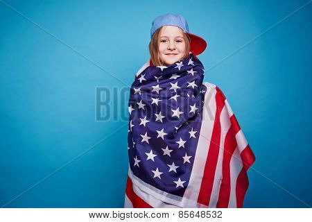 Cute girl wrapping in the American flag