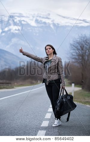 Traveler woman hitchhiking along lonely road.Pretty young woman tourist hitchhiking.Left alone