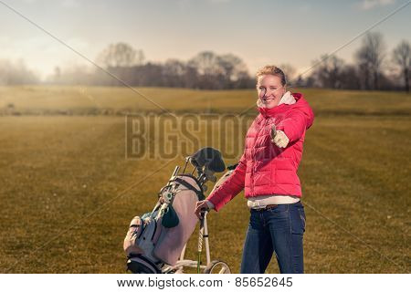 Smiling Happy Female Golfer Giving A Thumbs Up