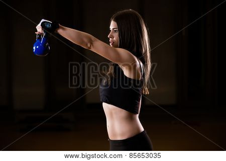 Young adult fitness woman doing exercises with a kettle bell as a part of a fitness workout.