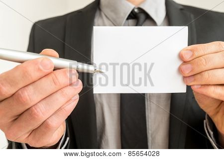 Businessman Holding Out A Blank Card And Pen
