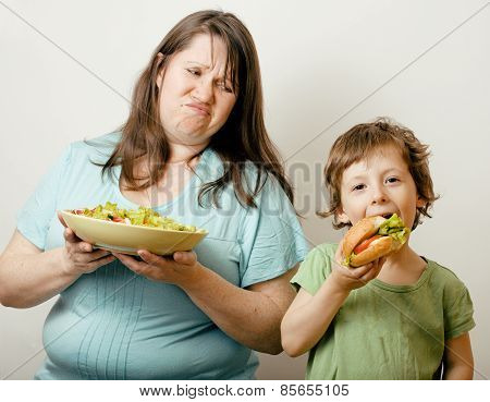 fat woman holding salad and little cute boy with hamburger teasi