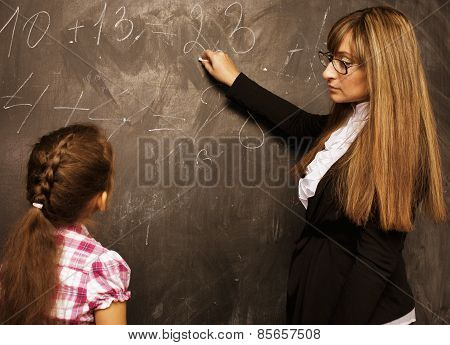teacher with pupil in classroom at blackboard writting, girl in