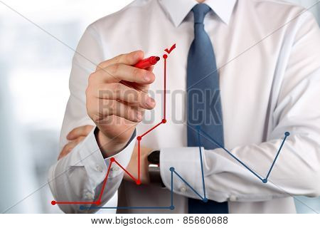 Young Business Man Drawing  A Graphs By Red Pen