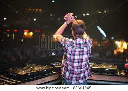 MOSCOW - APR 05, 2014: DJ applauding public and spinning the decks at the Trancemission in Stadium Live, view from the back