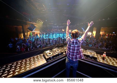 MOSCOW - APR 05, 2014: DJ in a plaid shirt with his arms raised spinning the decks at the Trancemission in Stadium Live, view from the back