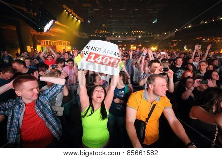 MOSCOW - APR 05, 2014: Happy young people with placards and mobile phone the Trancemission in Stadium Live