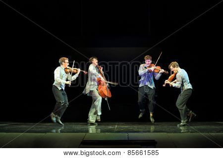 MOSCOW - MAR 12, 2014: Four funny actor Taper-show: dancing on the strings jumping with musical instruments on stage of the Palace on Yauza