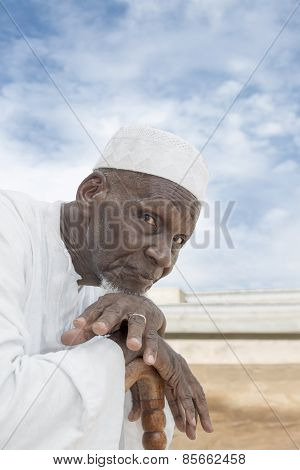 African man sitting in front of his house, eighty years old