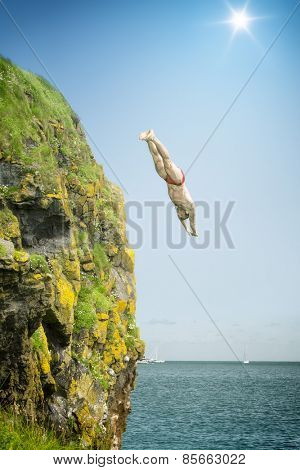 An image of a cliff jumper at the sea