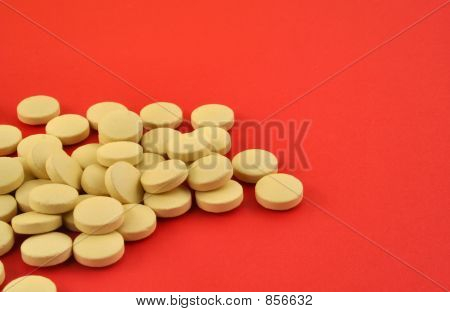 handful of yellow tablets on red 2