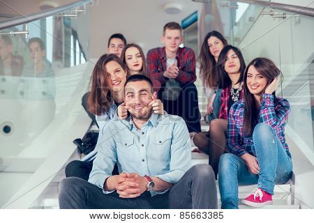 Happy teen girls and boys on the stairs school or college. Selective focus