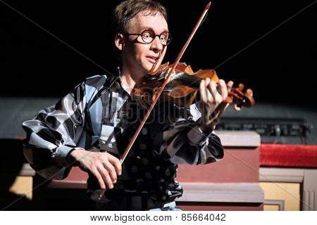 MOSCOW - MAR 12, 2014: Funny man in glasses Taper-show: dancing on the strings playing the violin on stage of the Palace on Yauza