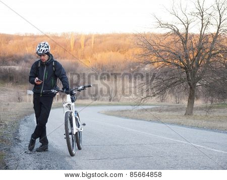 Man With Bicycle Standing On The Road And Looking At The Phone.