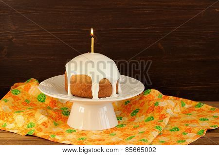 Kulich, Traditional Russian Easter Cake With Royal Icing And Lit Candle On White Pedestal