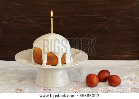 Kulich, Traditional Russian Easter Cake With Royal Icing, Lit Candle And Dyed Eggs On White Pedestal