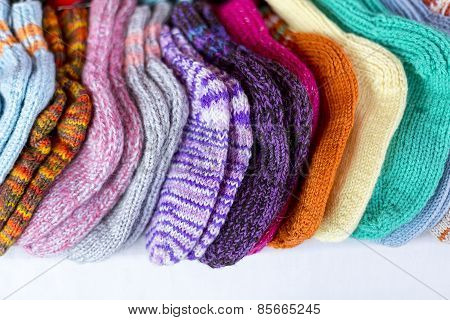 A  Row Of Multicolored Hand-knitted Baby Socks