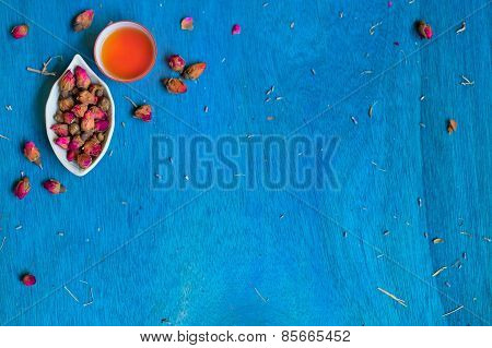 Teacup And Small Plate With Rose Buds On Blue Wooden Background.
