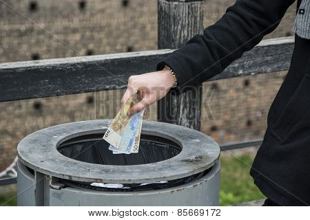 Hand Of Man Outdoors Throwing Banknotes In A Can