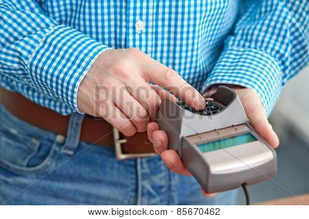 Male Hand Controls Payment Terminal