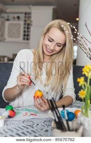 Beautiful young woman painting easter eggs
