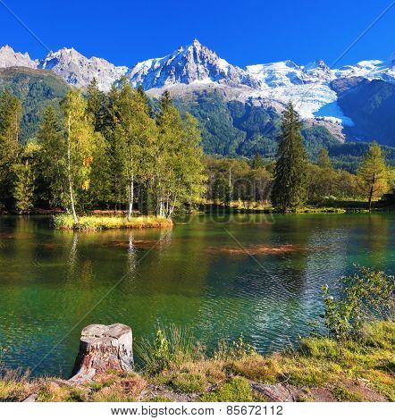 City park in the Alpine resort of Chamonix. Cold lake surrounded by trees and snow-capped mountains.