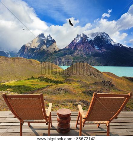 Wooden chairs in the park Torres del Paine. On the horizon is visible snow-covered rocky mountain. Pleasant holiday in Chile