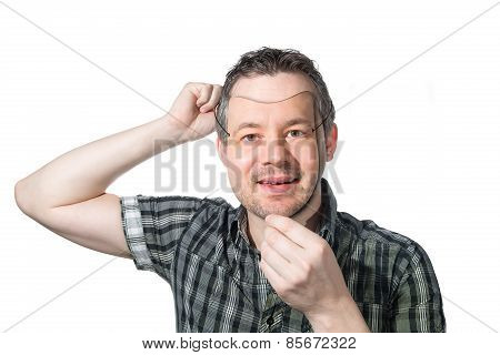 Man Putting On Mask Of Himself