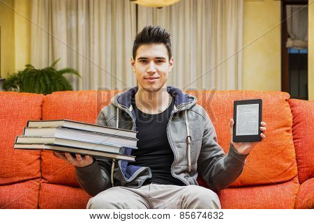 Young Man Showing Difference Between Ebook Reader And Heavy Books