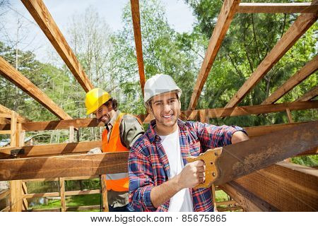 Portrait of happy construction worker cutting wood with handsaw while colleague in background at site