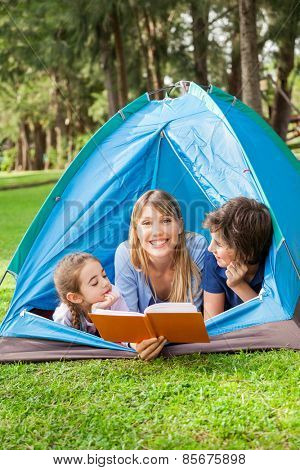 Portrait of happy mother reading book for children at campsite