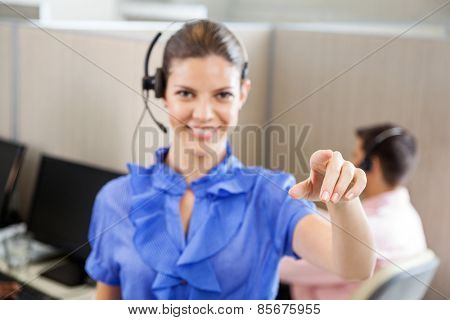 Portrait of smiling female call center employee pointing while colleague working in background at office