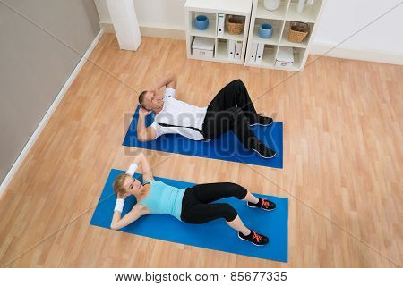 Young Couple Doing Crunches