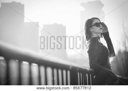 Rocker,punk woman.Young rock woman in black leather jacket casual standing with city background at s