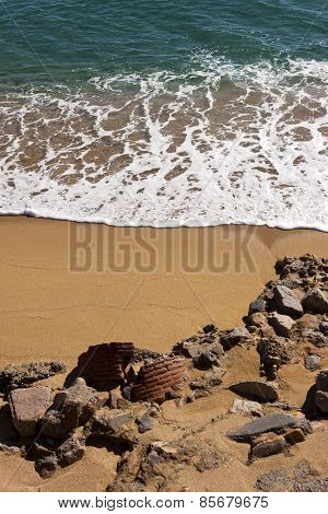 Wave Breaking In A Beach With Rocks And Ruins