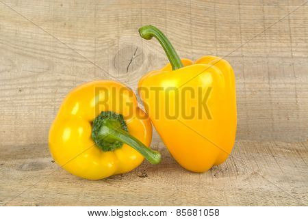 Studio Shot Of Yellow Bell Peppers On Wooden Plank