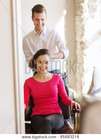 beauty, hairstyle and people concept - happy young woman with hairdresser finishing hairdo at salon