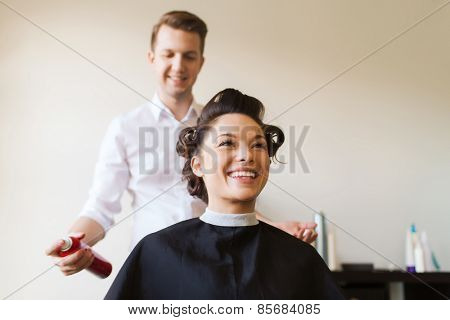 beauty, hairstyle and people concept - happy young woman with hairdresser with hair spray fixating hairdo at salon