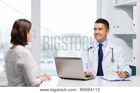 medicine, health care and people concept - smiling doctor with laptop computer and young woman meeting at hospital