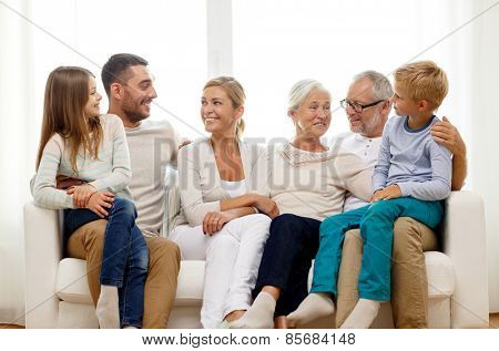 family, happiness, generation and people concept - happy family sitting on couch at home