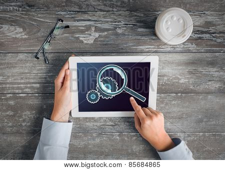 business, people, setting and technology concept - close up of hands pointing finger to tablet pc computer screen showing magnifier and cogwheel, coffee cup and eyeglasses on table