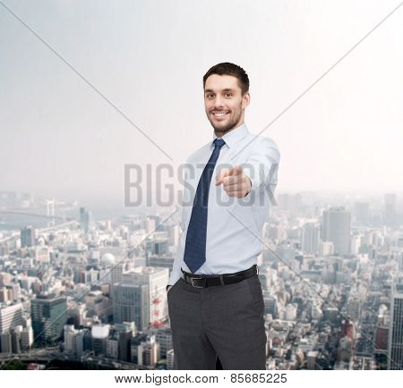 business, gesture and office concept - handsome businessman pointing finger at you