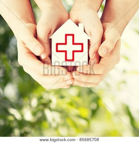 healthcare, medicine and charity concept - male and female hands holding white paper house
