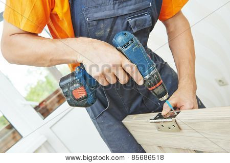 carpenter at interior wood door lock installation working with screwdriver