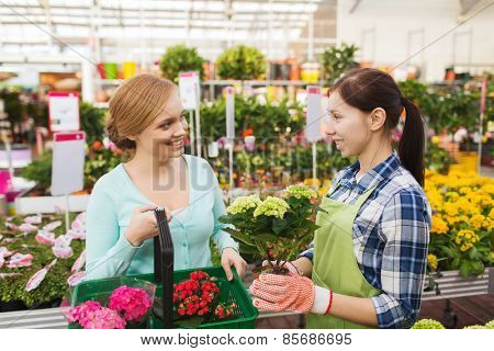 people, gardening, shopping, sale and consumerism concept - happy gardener helping woman with choosing flowers in greenhouse